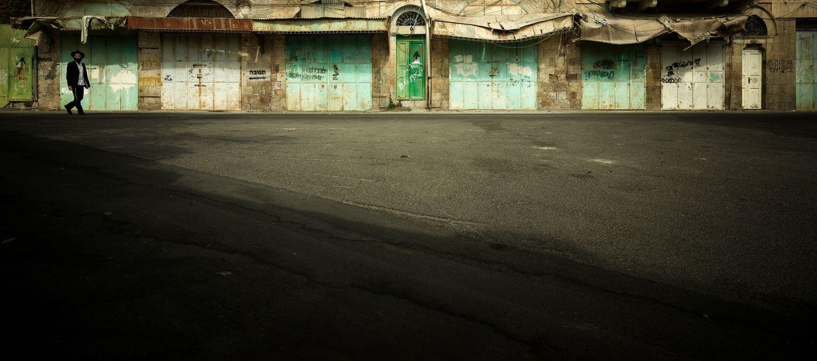 Marcheur solitaire de la rue Al-Shuhada, Vieille Ville d'Hébron, Patrimoine Mondial de l'Unesco, Palestine, 2018.  Autrefois lieu du ...