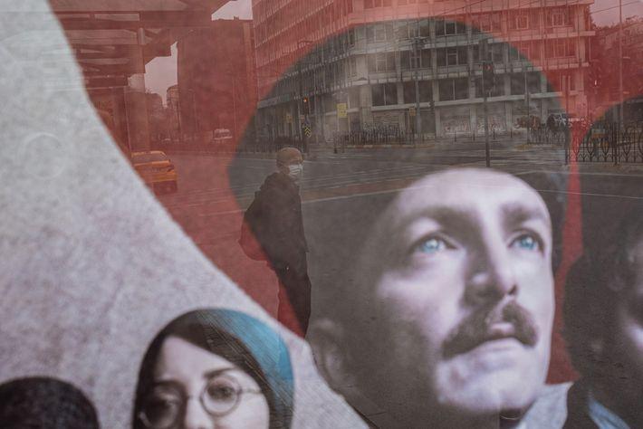 A une station de bus d'Istanbul, un homme portant un masque passe devant un panneau publicitaire ...