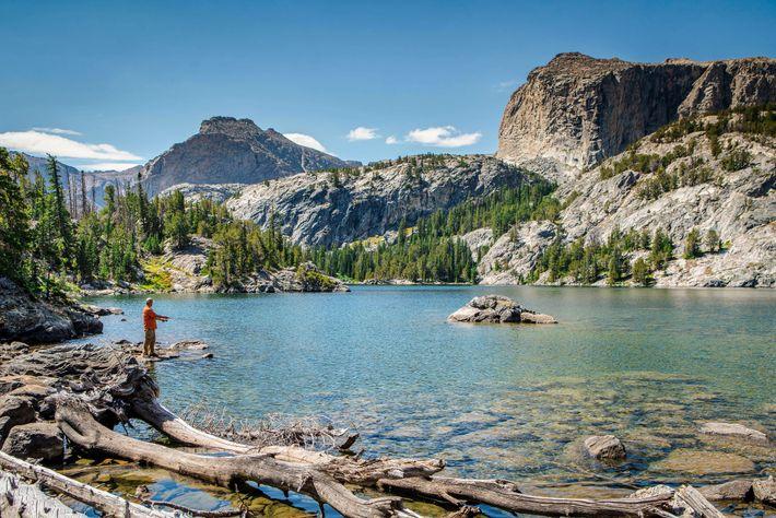 Un pêcheur tente d'attraper une truite dorée insaisissable dans un lac d'altitude de la chaîne de ...