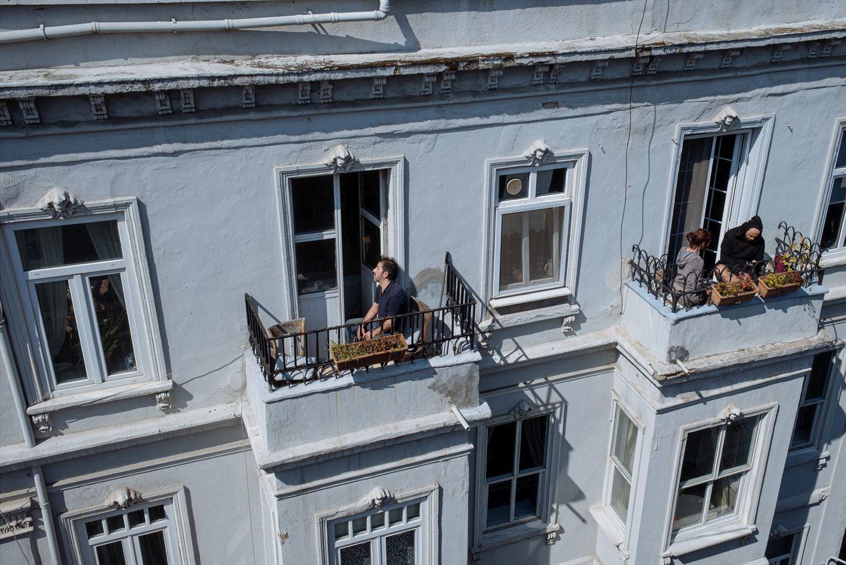 Dans le quartier de Beyoglu, des résidents prennent le soleil à leur balcon.