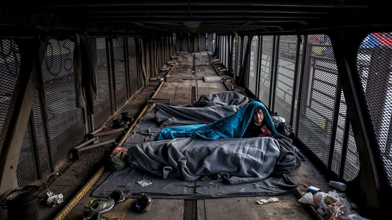 Shershah, 15 ans, d'Afghanistan, regarde au-dessous d'une couverture bleu clair dans un wagon abandonné de la ...