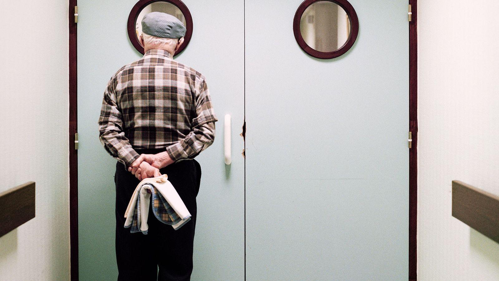 Un des résidents jette un œil à travers le hublot de la porte verrouillée qui marque ...