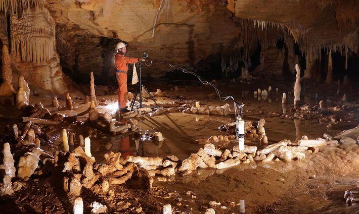 Dans la grotte de Bruniquel, en France, un ouvrier mesure des cercles de pierre susceptibles d'avoir ...