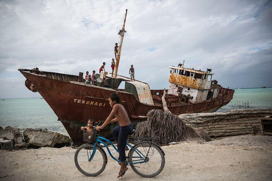 Aux Îles Gilbert, des enfants jouent à bord d'un navire rouillé, sur l'île de Betio, situé …