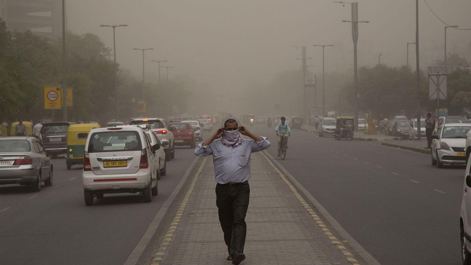 À New Delhi, en Inde, un homme se protège de la tempête de poussière qui enveloppe ...