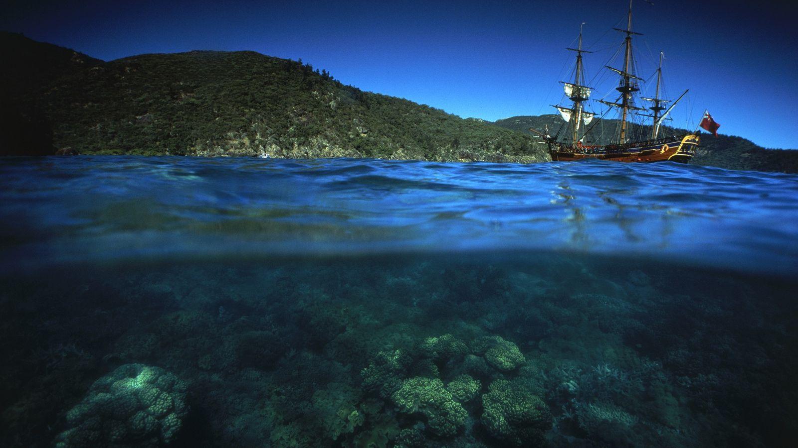 Ci-dessus, une reproduction moderne du trois-mâts HMB Endeavour navigue le long de la Grande Barrière de ...