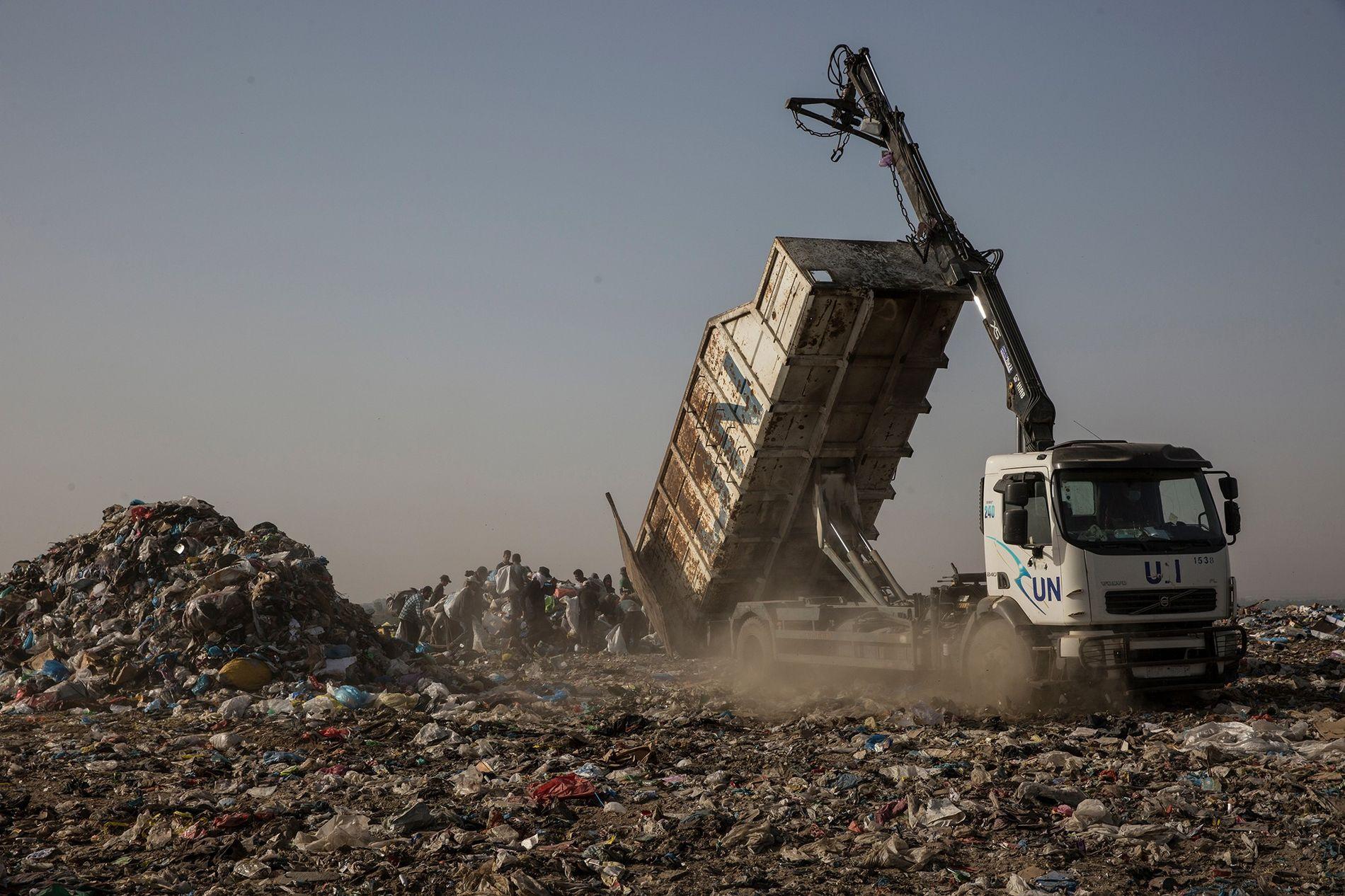 Un camion de l'ONU déverse des déchets sur un site situé à Juhor al-Deek, au sud-est de la ville de Gaza. De jeunes Palestiniens se rassemblent autour du camion pour fouiller le tas de détritus à la recherche de biens recyclables. Certains de ces travailleurs ont abandonné l'école et commencent leur journée avant l'aube pour gagner moins de 3 € par jour.