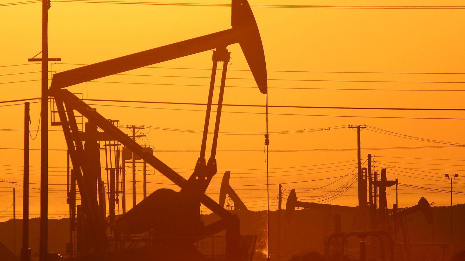 Cette photographie prise au crépuscule montre les chevalets de pompage des gisements de pétrole de la ...