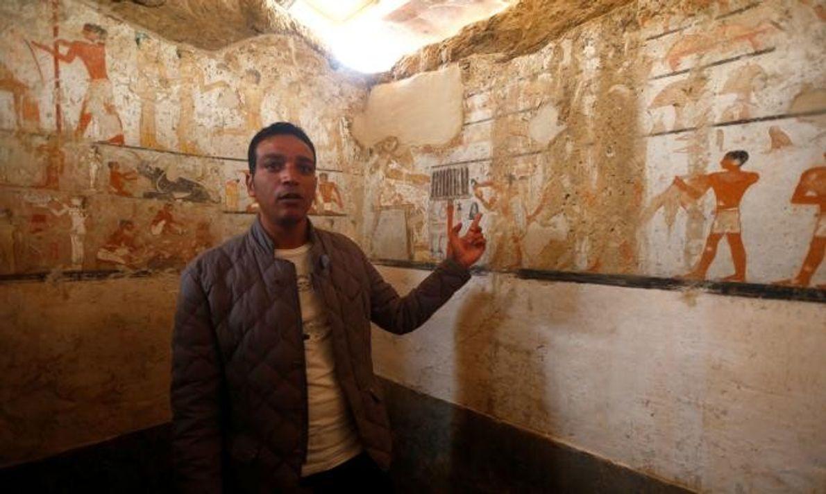 Un guide du ministère des antiquités égyptiennes inspecte les peintures murales décorant l'intérieur du tombeau de ...