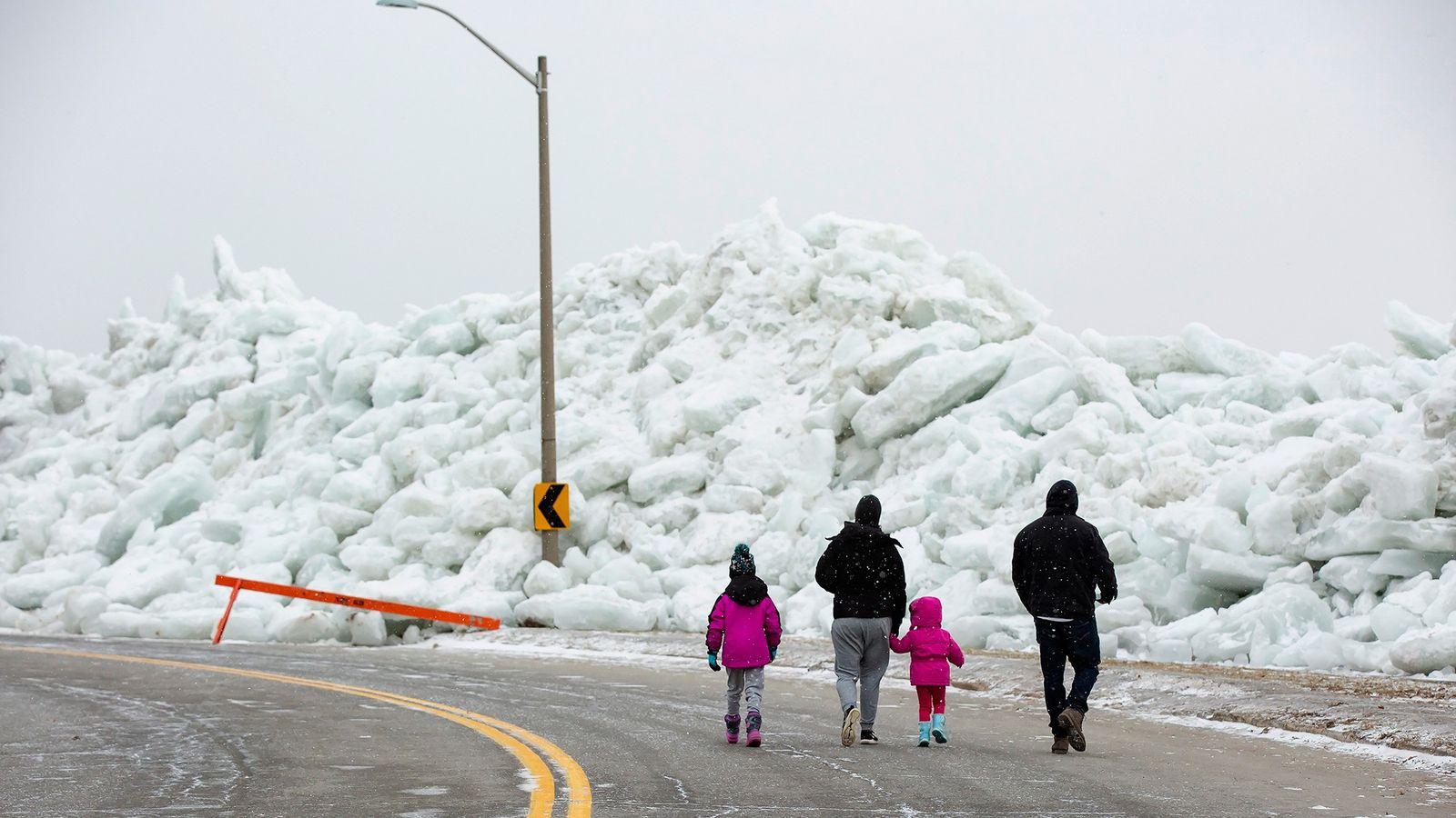 Une famille marchant près d'une accumulation massive de glace sur la rive du parc Mather à ...