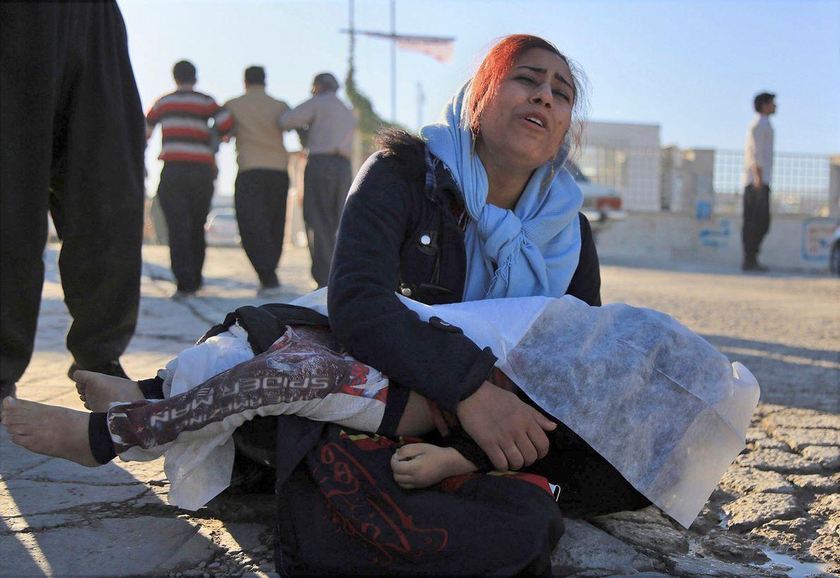 Cette femme pleure en tenant le corps de sa fille tuée par le tremblement de terre, ...