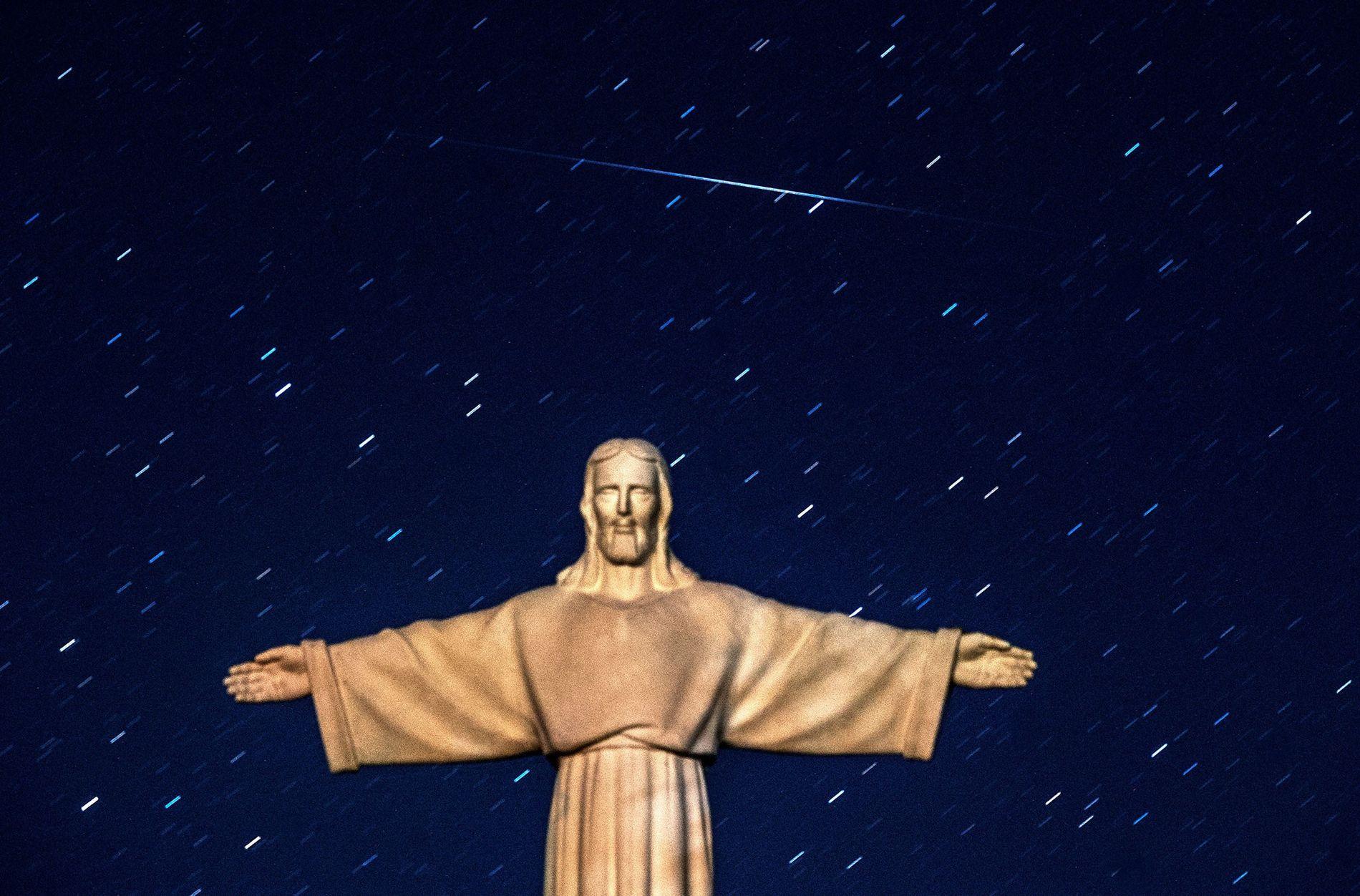 Le 13 août 2016, une météore des Perséïdes traverse le ciel nocturne au-dessus d'une statue de ...