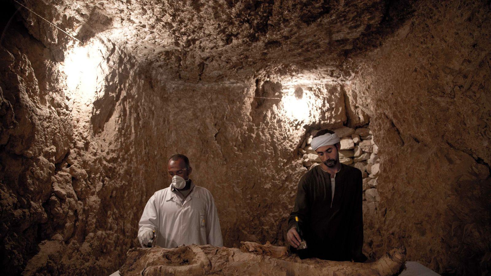Deux ouvriers prennent soin d'une momie découverte dans un tombeau de 3 500 ans, à Louxor.