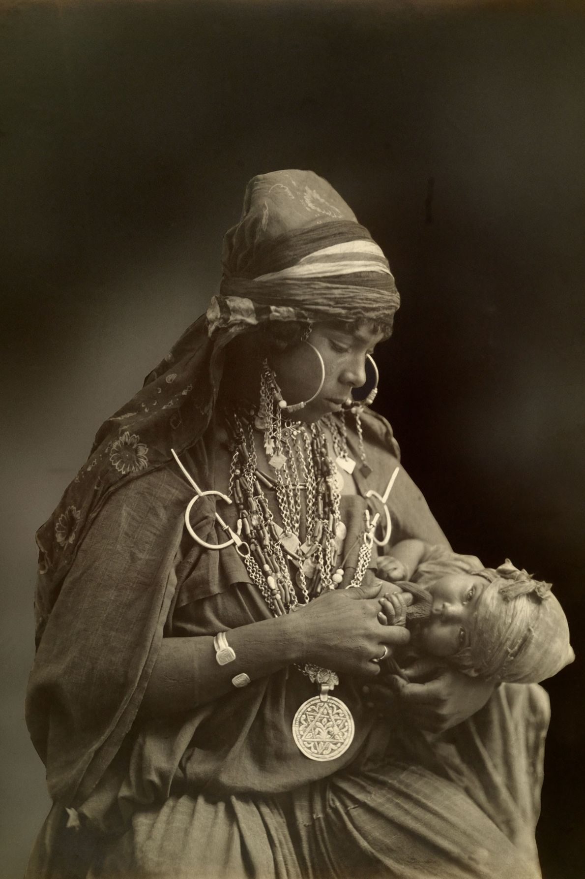 Une mère bédouine, portant de riches bijoux, veille sur son bébé au début des années 1900.