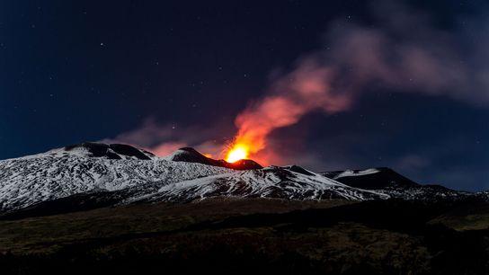 Des coulées de lave illuminent les flancs du Mont Etna, en Sicile, durant l'impressionnante éruption de ...