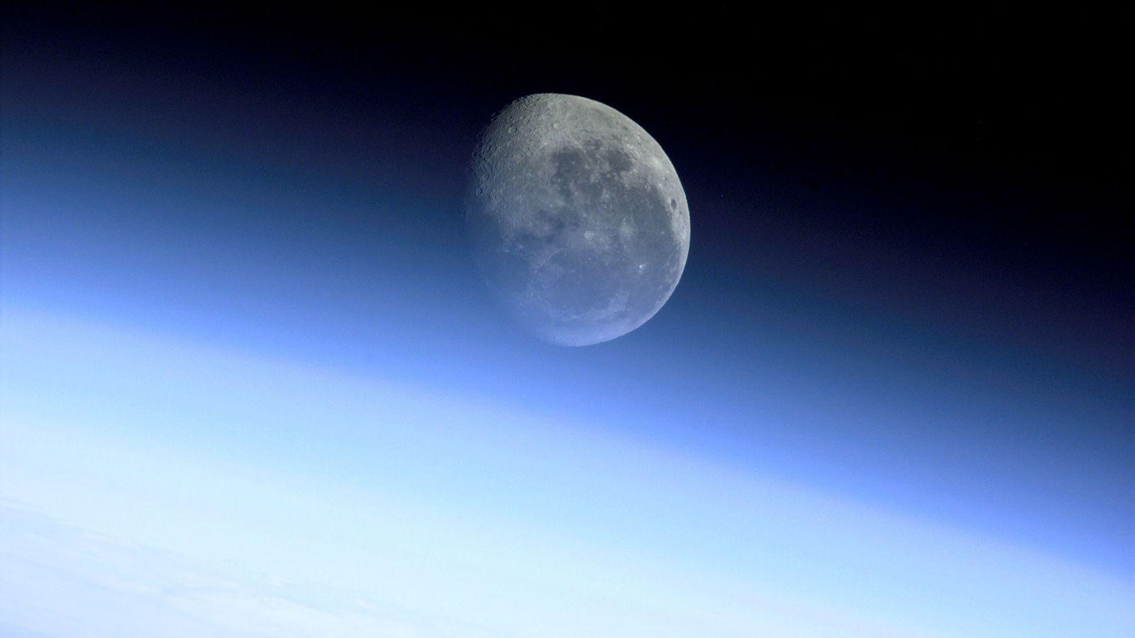 La lune brille à travers l'atmosphère de la Terre sur cette photo prise depuis la navette ...
