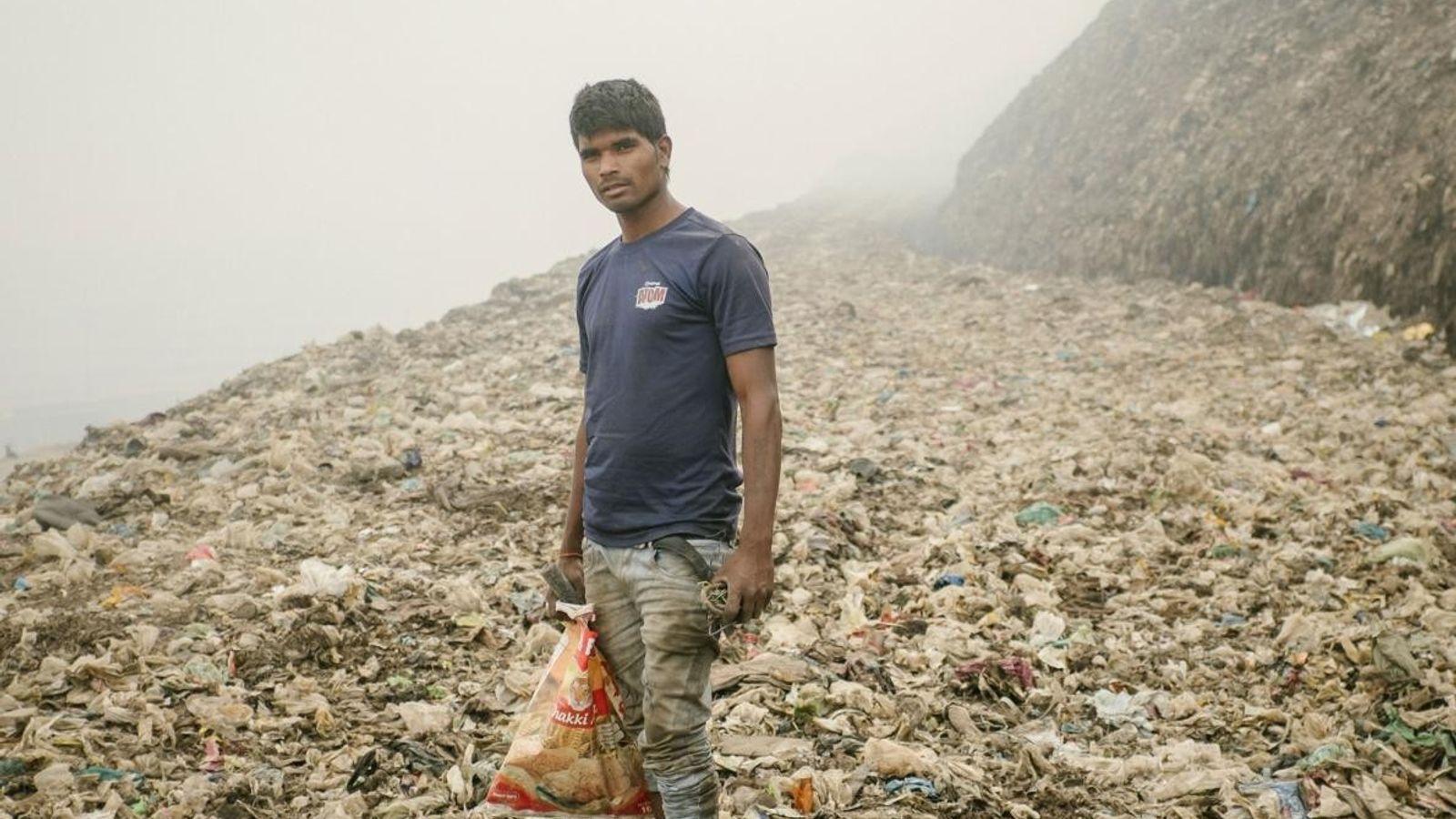 Un recycleur à la recherche de métal à Bhalswa, une décharge géante qui brûle constamment et ...
