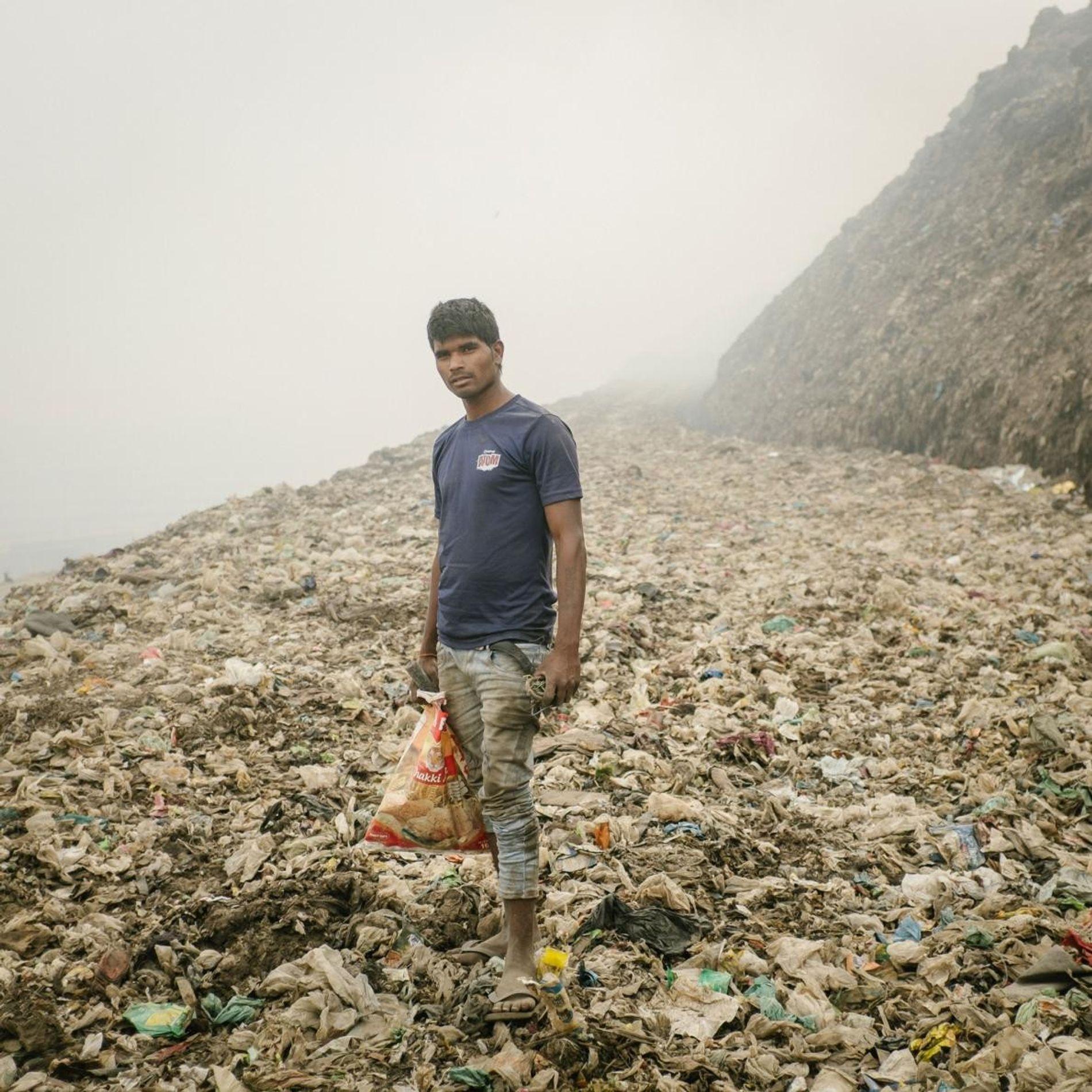 Un recycleur à la recherche de métal à Bhalswa, une décharge géante qui brûle constamment et émet des gaz toxiques.