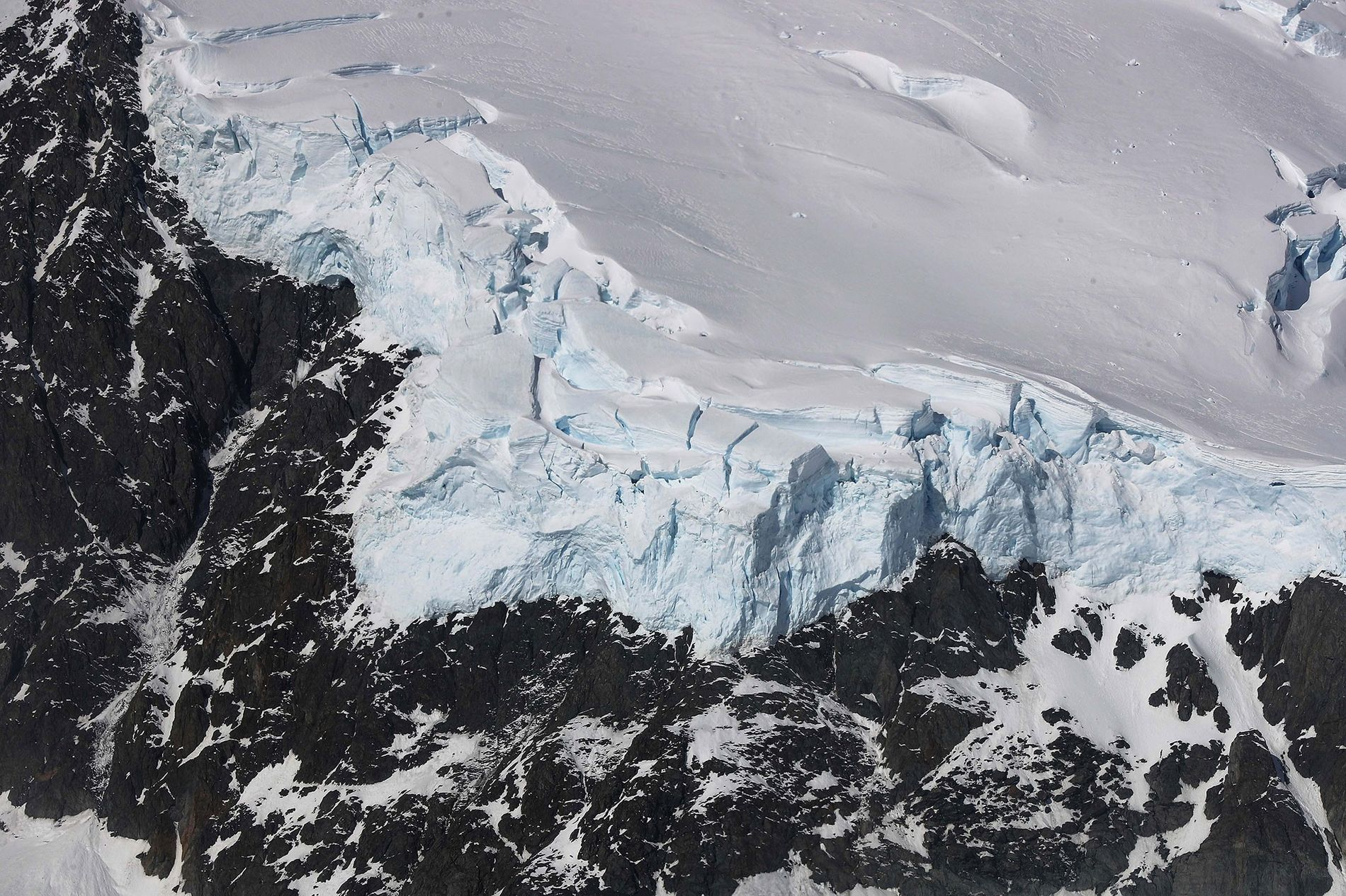 """La glace rencontre la roche dans la péninsule antarctique, sur une photo prise dans le cadre de l'opération IceBridge de la NASA en octobre 2017. Il y a des millions d'années, la planète entière aurait pu ressembler à cette scène polaire au cours d'une phase appelée """"La Terre Boule de Neige""""."""