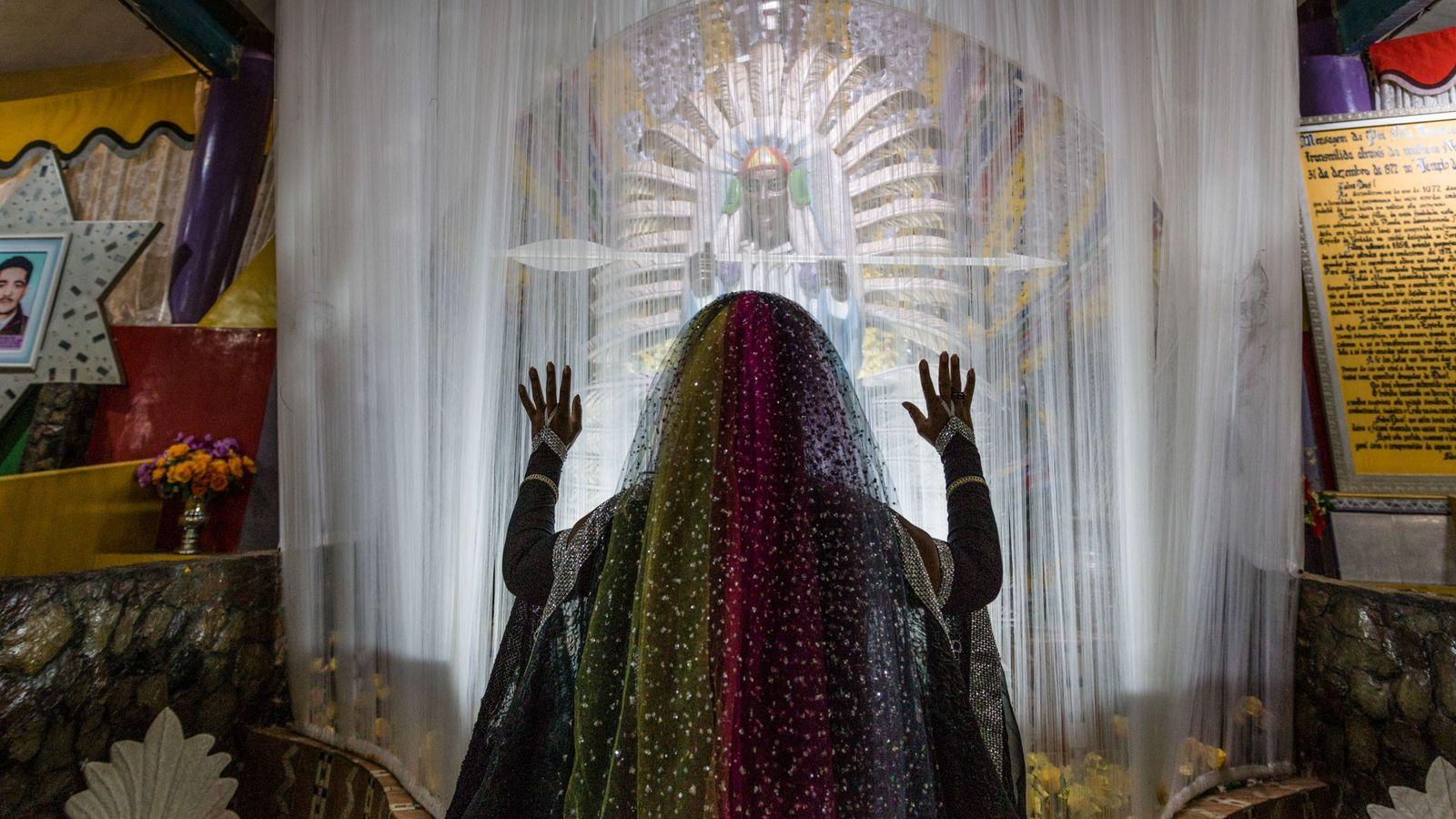 Une adepte de la Vallée de l'aurore prie devant une statue de l'un des chefs spirituels, ...