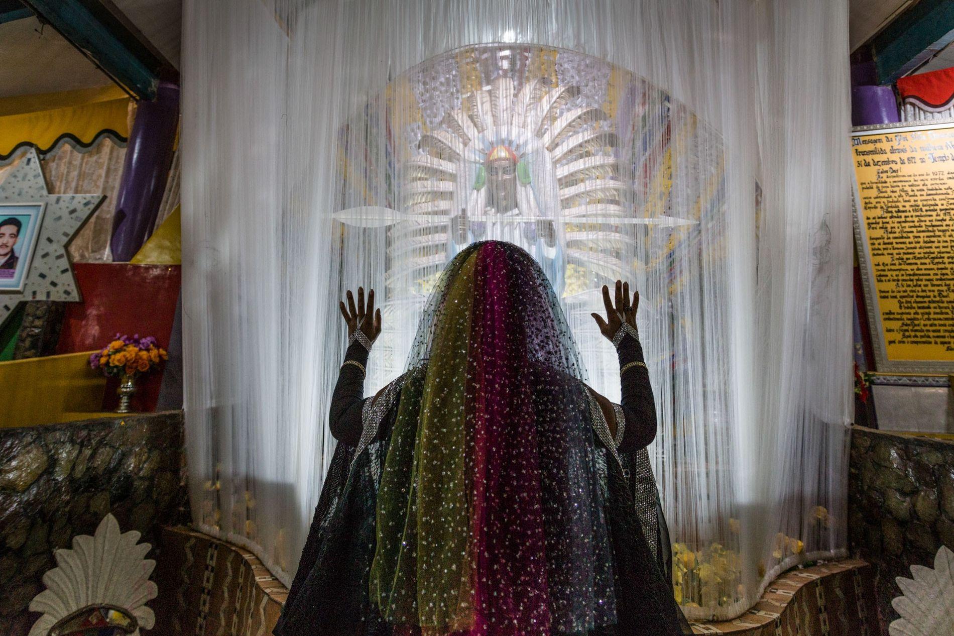 Une adepte de la Vallée de l'aurore prie devant une statue de l'un des chefs spirituels, le chef de la Flêche Blanche.
