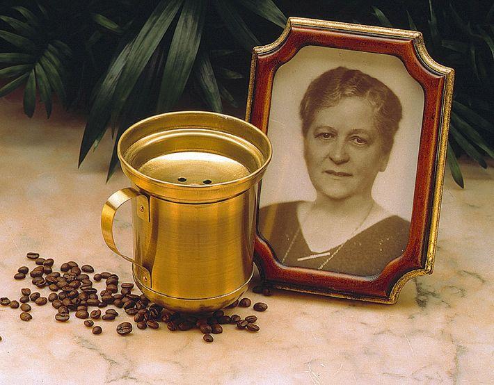 Photographie de Melitta Bentz, accompagnée de grains de café et d'une tasse en laiton.