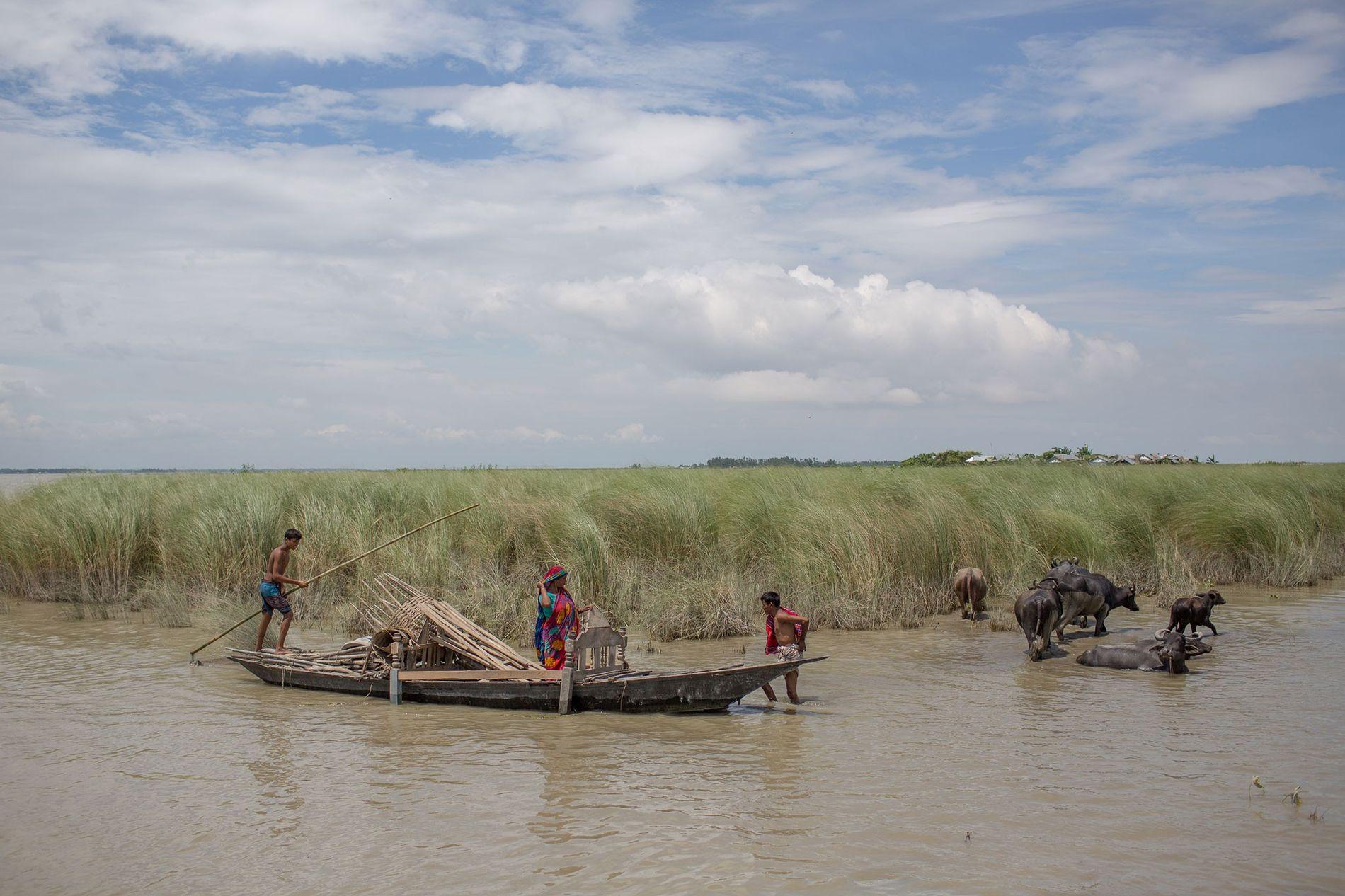 Des habitants d' un village touché par les inondations transportent leurs biens importants par bateau à ...