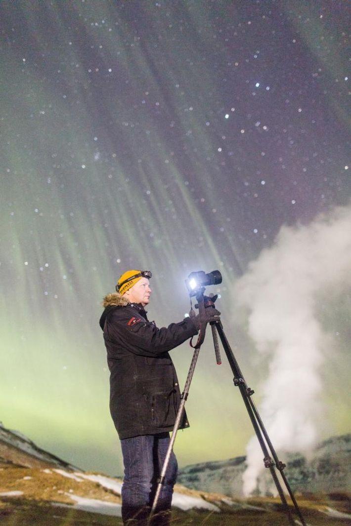 Le chasseur d'aurores Gaukur Hjartarson prend des photos près de Húsavík, une ville située sur la ...