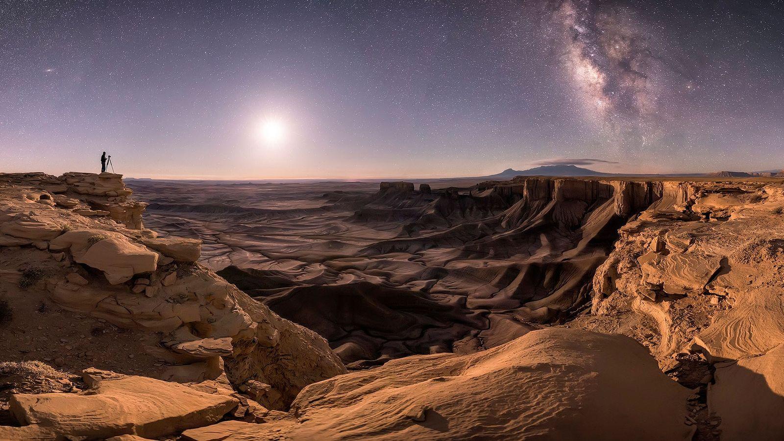 Un photographe solitaire installe son matériel à Moab, dans l'Utah, sa silhouette est tracée par le ...