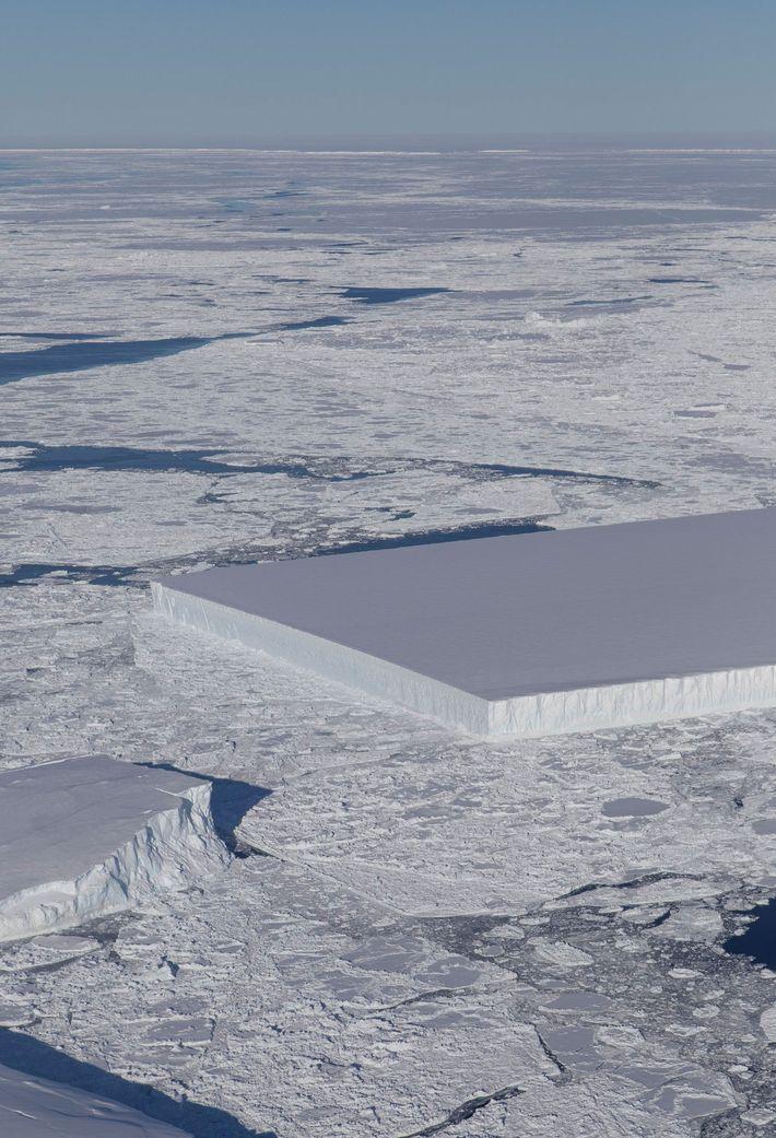Un iceberg tabulaire est visible à droite, flottant dans une mer de glace, juste à côté ...