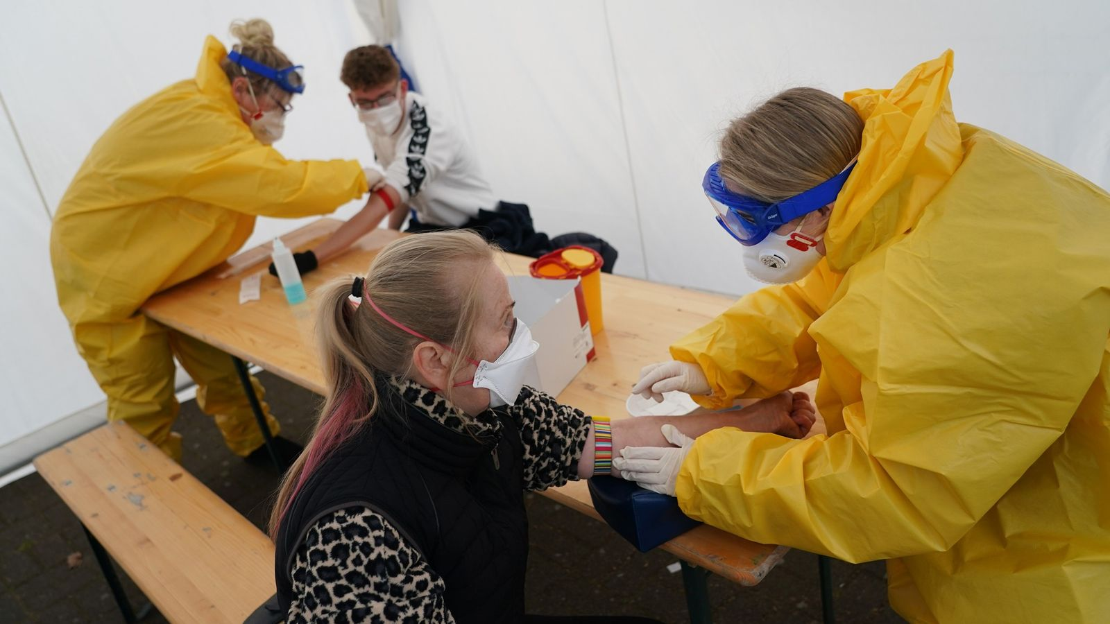 Après avoir enfilé combinaison, masque, gants et lunettes de protection, des soignants volontaires réalisent des prises ...