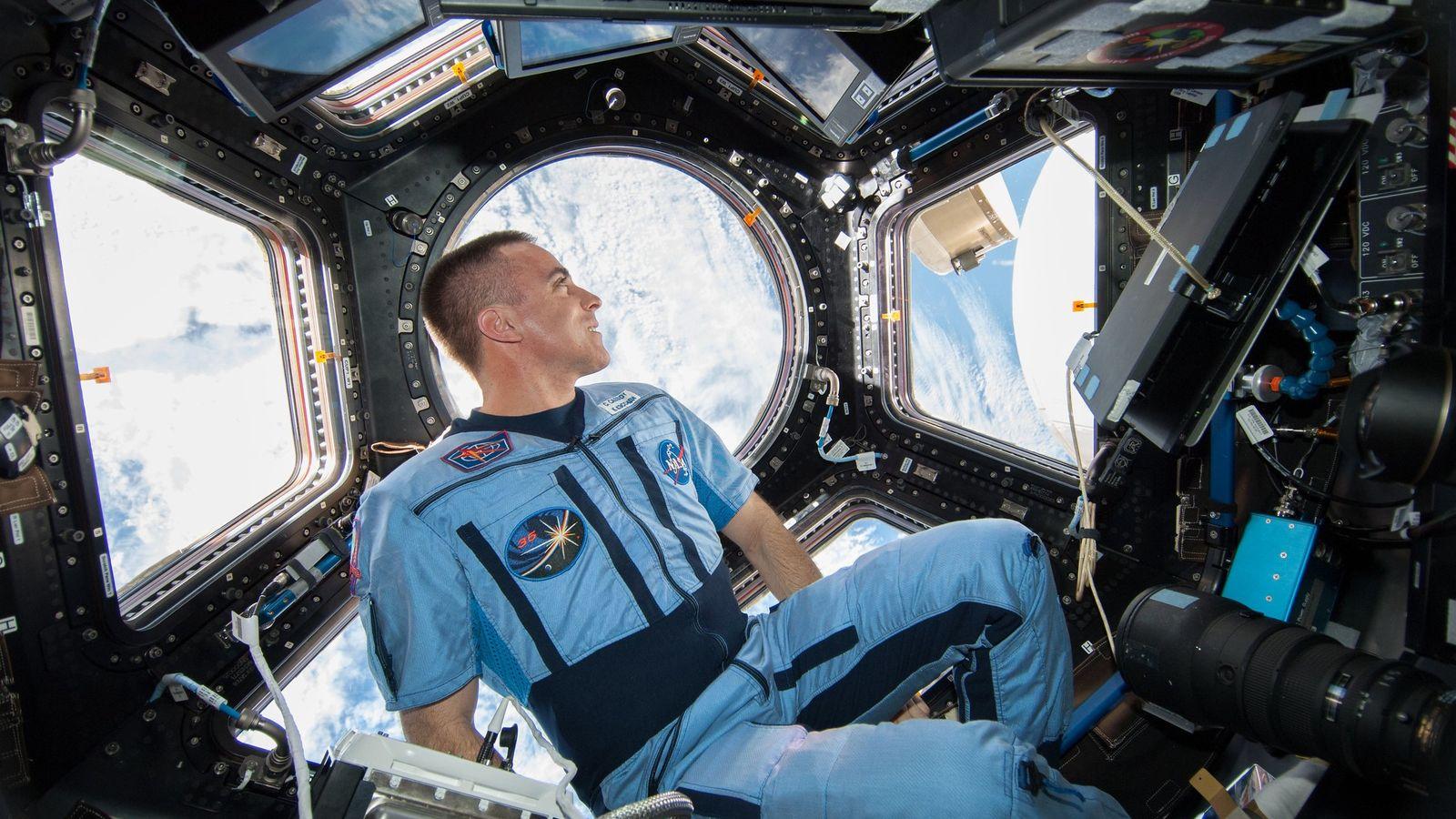 En août 2013, l'astronaute de la NASA Chris Cassidy regarde à travers la coupole d'observation panoramique ...