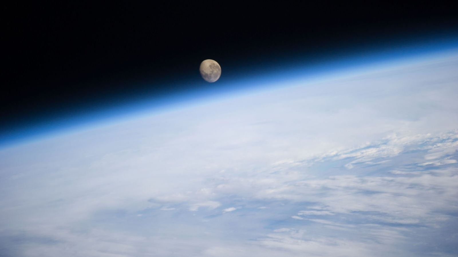 The moon sets over the Earth, as seen from the International Space Station.