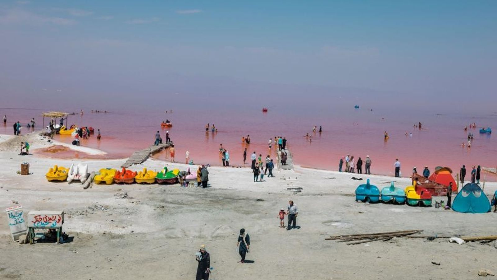 Les baigneurs pataugent dans les eaux colorées de rouge par des bactéries et des algues. Des ...