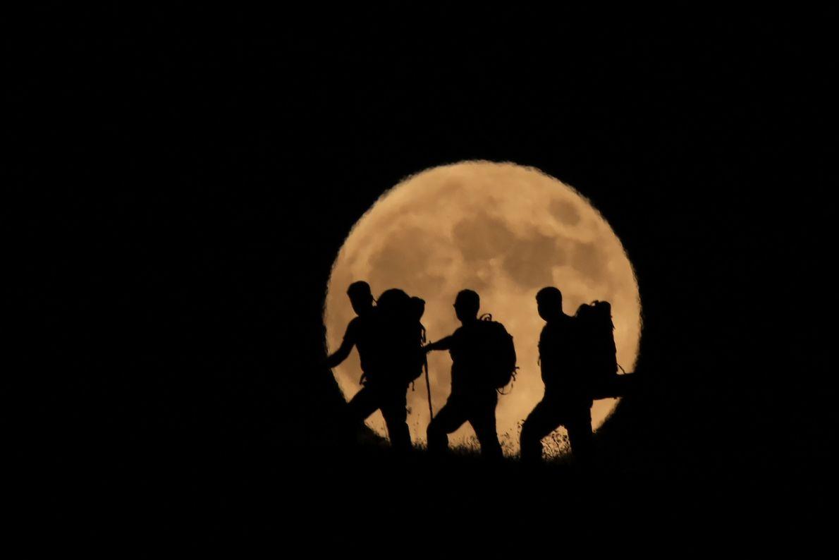 La pleine lune se lève derrière les silhouettes d'alpinistes grimpant le mont Artos, dans la province ...