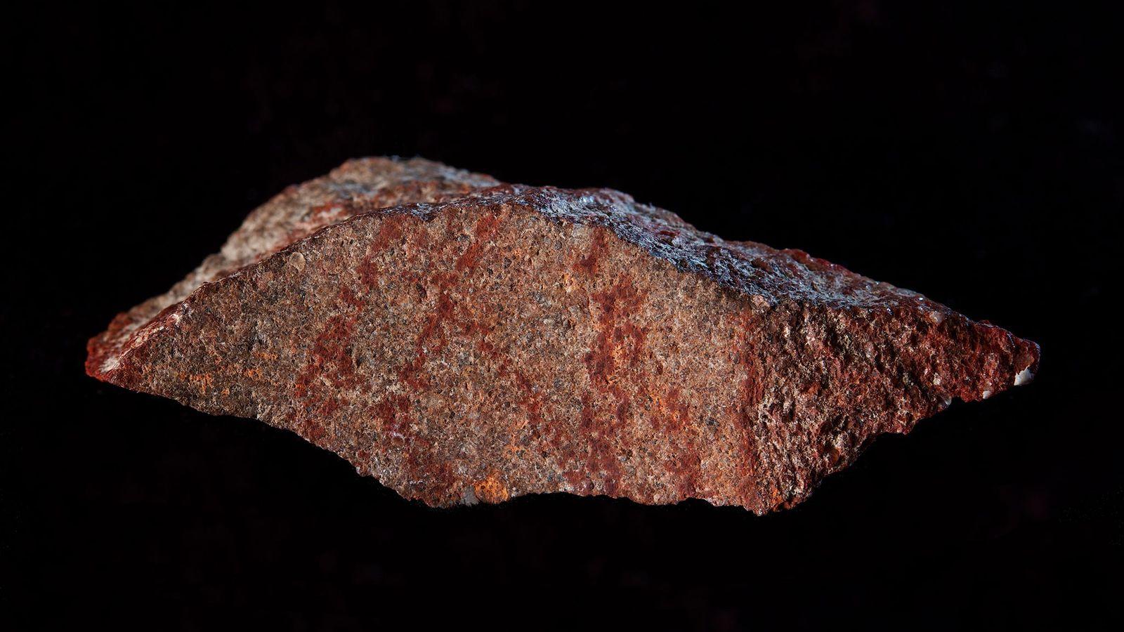 Ce fragment de pierre marqué à l'ocre a été découvert dans la grotte de Blombos, en ...