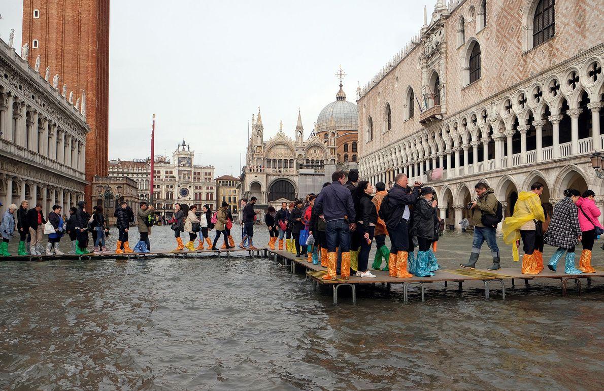 Des passants marchent sur une passerelle installée sur la place Saint-Marc inondée pendant une saison d'acqua ...