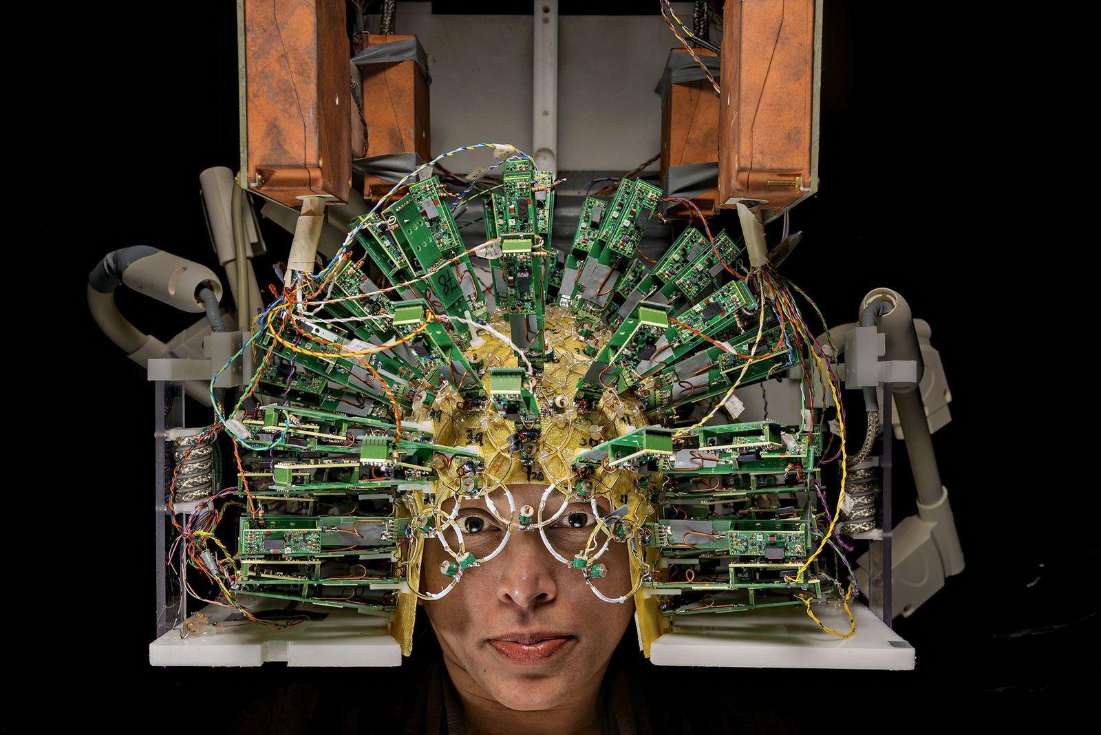 Un ingénieur porte un casque muni de capteurs pour passer un scanner cérébral, au Centre Martinos ...