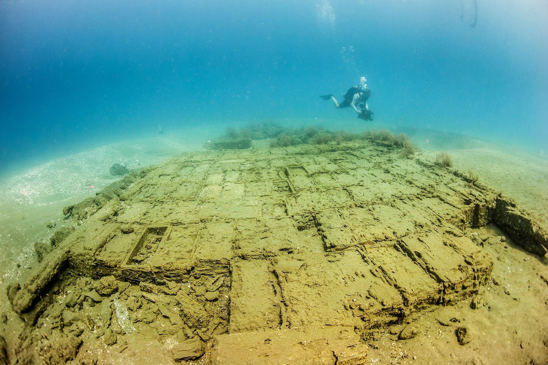 Un plongeur inspecte des caisses en bois dans l'épave du navire espagnol du 17e siècle, découverte ...