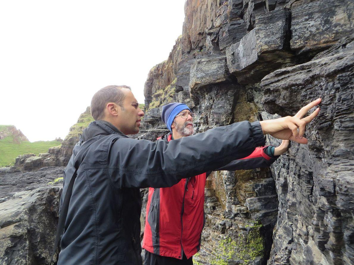Steve Brusatte (à gauche) et Mark Wilkinson étudient avec attention la falaise située à côté des ...