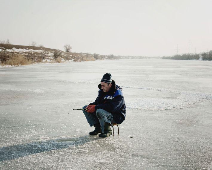 Pendant l'hiver, un homme pêche à travers un petit trou sur la rivière gelée Ialpug.