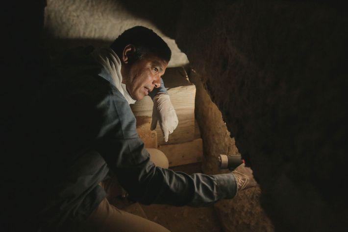Ramadan Hussein regarde à l'intérieur d'un sarcophage en pierre à la recherche de momies. L'équipe en ...