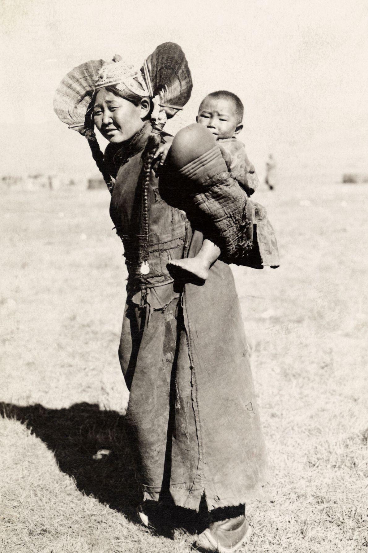 Vêtue de vêtements traditionnels, une femme du nord de la Mongolie porte son fils sur le ...
