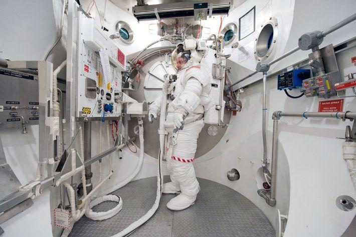 Scott Kelly se tient dans une Extravehicular Mobility Unit (EMU) lors d'un entraînement sur Terre en ...