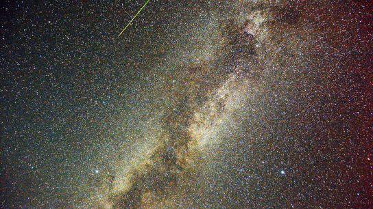 Sur cette image avec exposition multiple, un météore des Perséides trace une ligne verte dans le ...