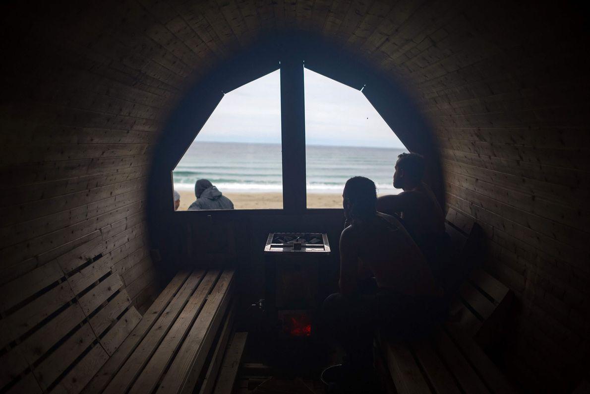 Des surfeurs se réchauffent dans un sauna pendant les Lofoten Masters, la compétition de surf la ...