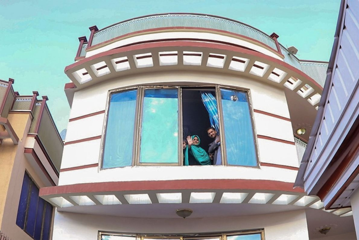 Sharbat Gula salue par la fenêtre de sa nouvelle maison. Le gouvernement afghan lui verse une ...