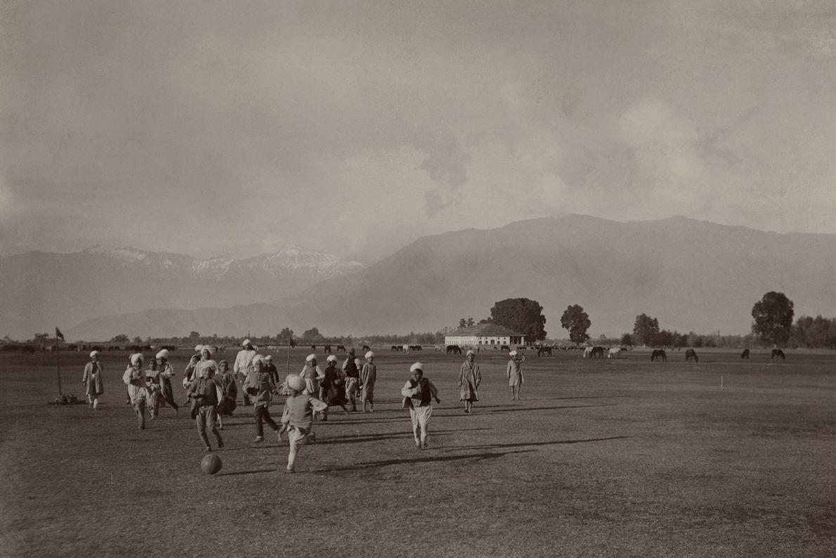 Des enfants jouent au football dans une vaste plaine au pied de l'Himalaya.