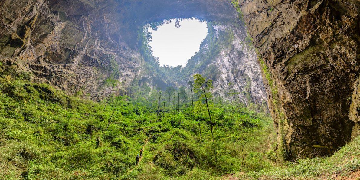 Deux personnes se promènent dans une doline de la plus grande grotte au monde, Son Doong. ...