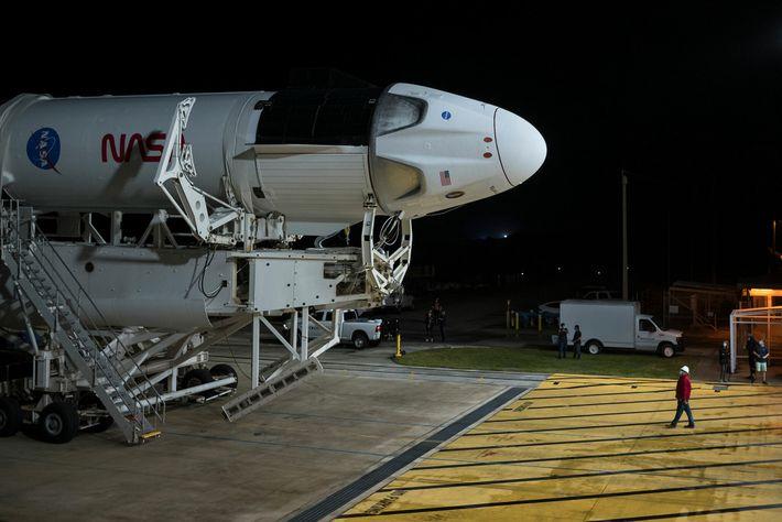 Une fusée Falcon 9 de SpaceX, dotée du vaisseau spatial Crew Dragon, sort en roulant de l'installation d'intégration ...